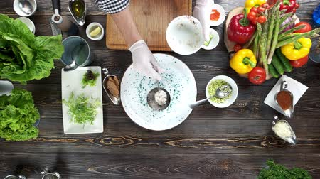 chefs table : Hands making food, herring tartare. Dinner preparation, wooden table.