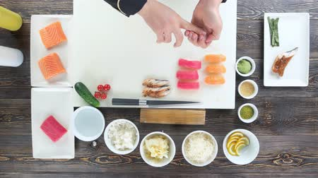 нигири : Sushi ingredients on wooden table. Food preparation, japanese cuisine.