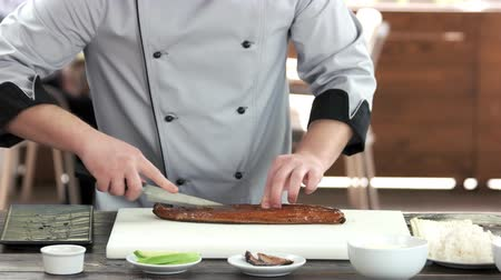 унаги : Chef cutting smoked fish. Man in uniform preparing food.