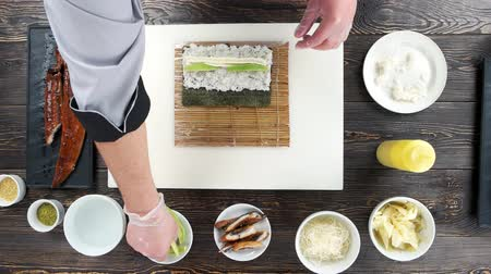 унаги : Hands making a sushi roll. Rice, cream cheese and avocado.