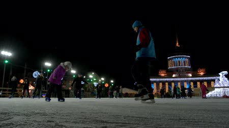 el feneri : 21.01.2017 - Kiev, Ukraine. Woman is teaching her daughter how to skate. Snowfall on the ice rink. Stok Video