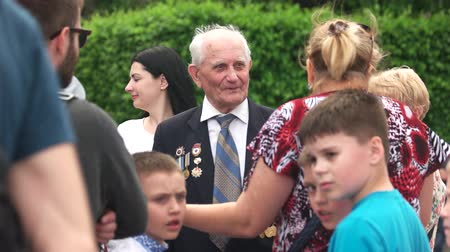 честь : 09.05.2018, Ukraine, Kiev. People congratulate old senior veteran with victory day. 9 may, second world war veteran with medals. Стоковые видеозаписи