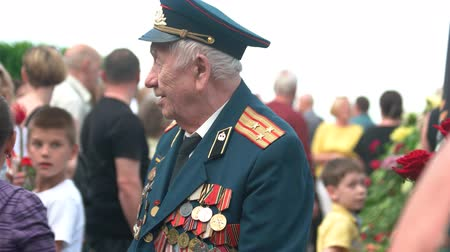medal : 09.05.2018, Ukraine, Kiev. Little girl hugs with old veteran of World War II. Celebrating victory day outdoors.