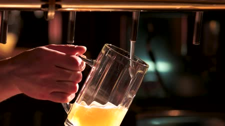 frothy : Close-up filling beer from beer pump. Barman hand pouring a lager beer in a glass.