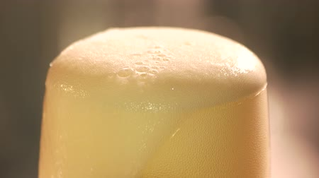 túlcsordulás : Beer foam cutting with knife, close up. Cutting beer froth, macro view.