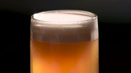 rotational : Glass full of beer with foam rotating. Glass of beer expositing from every side, close up.