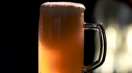 overfill : Pouring juice in thick beer. Cold Light Beer in a glass with water drops.