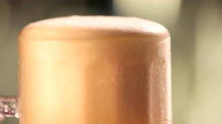 overfill : Beer foam motion. Slowly dripping beer foam out of glass, close up.