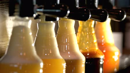 plastic cups : Plastic bottles with different beer styles. Close up bartender pouring plastic bottles from beer tap behind bar. Stock Footage