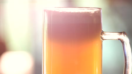 overfill : Rotating glass of ale. Head of glass of craft lager beer.