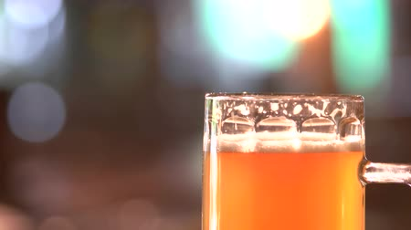 overfill : Thick orange beer head. Close up beer head rotating. Low foam beer rotating in blurred background. Stock Footage