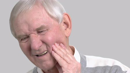 duyarlı : Older man with the tooth pain, toothache. Male senior suffering from terrible toothache on grey background. Sick old man.