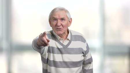 descontente : Angry older man arguing and pointing with finger. Senior man expresses his dissatisfaction, blurred background. Pensioner defends his rights.