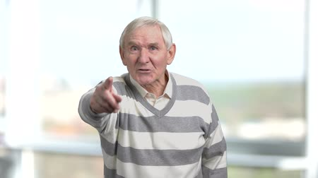 descontente : Irritated elderly man, blurred background. Angry senior man arguing and gesturing with finger. Man angrily talking to camera.