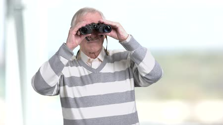 teleskop : Elderly man with binoculars, blurred background. Senior man looking through binoculars. Stok Video