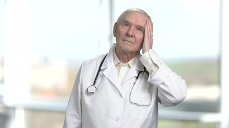 хмурый : Old doctor get rid of excessive sweating. Portrait of frowning senior doctor with stethoscope. Bright windows background.