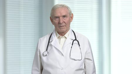 хмурый : Stressed old angry physician having headache. Senior health care professional doctor with stethoscope. Blurred windows with louvers background.