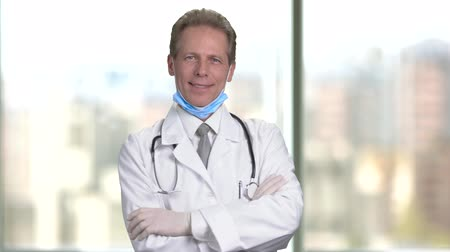 protective suit : Mature middle aged smiling doctor folding arms. Bright abstract blurred windows background with view on city. Stock Footage