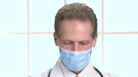 protective suit : Serious intense doctor face in blue mask working. Mature male surgeon, close up. Big bright checkered framed windows background. Stock Footage
