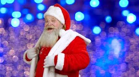 santaclaus : Joyful Santa Claus is dancing on blue background. Happy bearded Santa Claus on bokeh background. Winter holiday atmosphere. Stock Footage