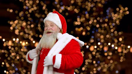 santaclaus : Santa Claus in red costume is dancing. Old authentic Santa Claus with christmas hat is dancing on shimmering lights background. Winter holiday celebration.