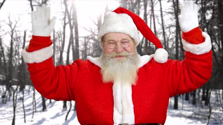 santaclaus : Portrait of authentic Santa Claus waving with hands. Senior man in costume of Santa Claus with greeting gesture outdoors. Christmas holiday atmosphere.