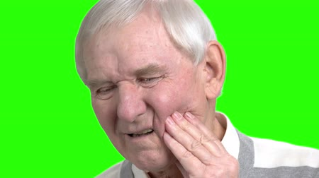 pena : Close up old man massaging touching his cheek. Grandpa touching his cheeck because of teeth pain, close up, green hromakey backgorund.