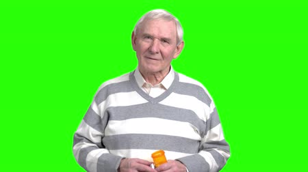 repentance : Smiling old man with can pills. Grandpa holding can with painkillers in green background.