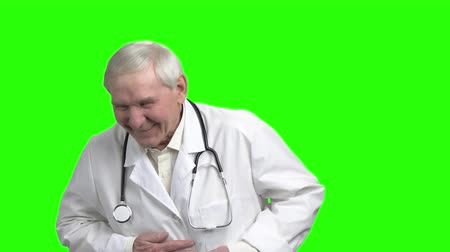 maturità : Old laughing doctor, slow-motion. Happy old male doctor, green hroma background.