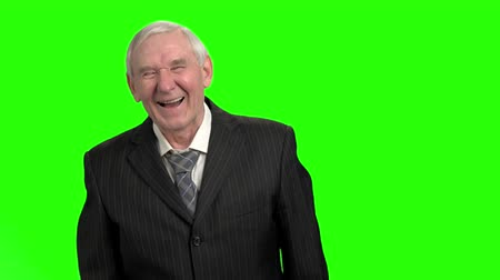 energized : Old man in black suit laughing hard, slow-motion. Grandpa laughing out loud against green hromakey background.
