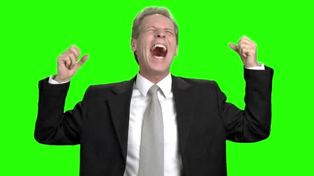 overwrought : Business man heartily cheering with his mouth open. Successful businessman with raising hands yelling, green background.