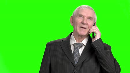 energized : Old businessman talking on phone. Portrait of senior businessman in suit talking on phone, green hroma screen background.