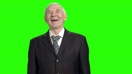 energized : Portrait of happy politician laughing hard. Laughing 90 year old senior man in suit portrait in green hromakey background.