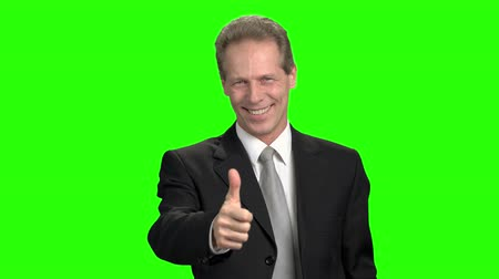 energized : Portrait of middle aged man in suit with thumb up. Thumb up from cheerful businessman, green screen hromakey background. Stock Footage