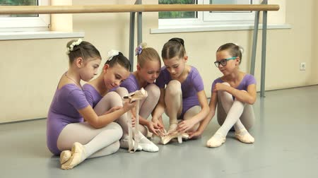 yetenekli : Pretty ballet-dancers and ballet studio. Group of little ballerinas sitting on the floor and having a rest. School of classical ballet.