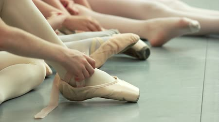 тапки : Group of young ballerinas taking off pointe shoes. Little caucasian ballet-dancer untie her ballet slippers. Ballet dance classes.