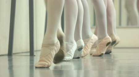 classical suit : Legs of ballet girls in pointes. Faceless girls leg in ballet shoes making position on the floor. Legs position in ballet. Stock Footage