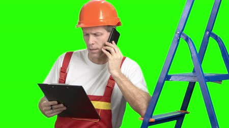 alpha cell : Serious foremen talking on mobile phone. Construction inspector looking on project in clipboard and talking on mobile phone. Discussing new project.