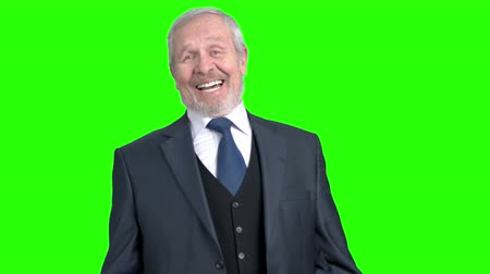 вырезка : Elderly businessman laughing on green screen. Emotional old man in formal wear laughing on chroma key background. Human facial expressions.