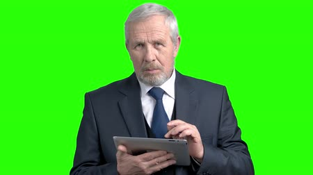 competence : Serious senior businessman using pc tablet. Confident elderly male executive working on computer tablet, chroma key background.