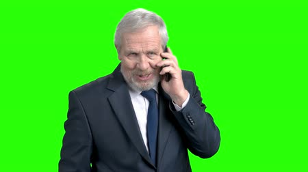 alpha cell : Smiling businessman talking on mobile phone. Cheerful senior male executive talking on mobile phone, green screen. Business people and mobile communication.