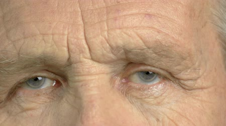 crinkle : Close up old man closed eyes. Detail of eyes of elderly wrinkled man. Smiling face and eyes emotion.