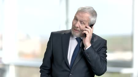 リーダーシップ : Senior businessman talking on phone. Confident elderly businessman talking on smartphone of blurred background. People, bussiness and communication. 動画素材