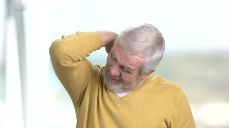 csípés : Older man having terrible neck pain. Stressed senior man suffering from strong ache in neck, blurred background.