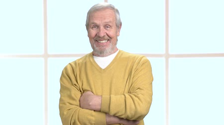 сложены : Senior smiling man with crossed arms. Handsome elderly man smiling and looking at camera with folded arms, window background.