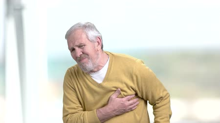 infarction : Man having discomfort in chest. Elderly man going taking pills from heart pain. Stress affects the body. Stock Footage