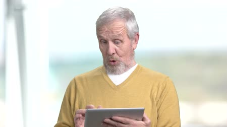 starszy pan : Funny elderly man with pc tablet. Happy smiling grandpa using digital tablet on blurred background. Senior people and modern technology.