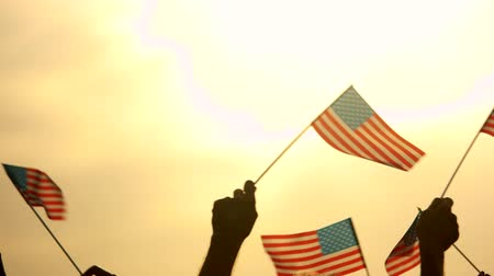 июль : Close up American flags in peoples hands. Patriotic people raised USA flags to the evening sky. Concept of country Independence.