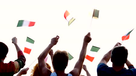 concert crowd : Hands waving with flags of Italy. Back view group of patriotic Italian people holding small flags. Italian patriotic party. Stock Footage