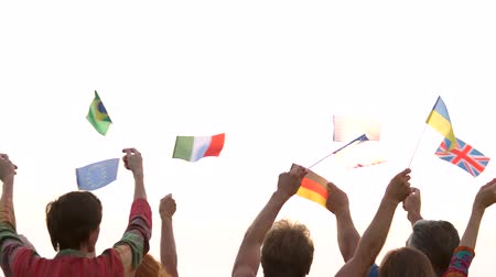 indie : People waving different flags outdoors. Crowd of international people. Morning sky background.